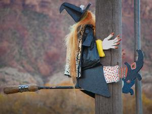 USA, Utah, Moab, Halloween witch on broomstick that crashed into pole. by Merrill Images
