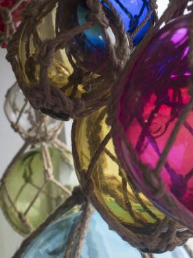 USA, Washington State, Whidbey Island, Coupeville. Colorful glass fishing net floats by Merrill Images