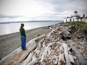 Woman Standing on Driftwood and Looking Towards Discovery Park Lighthouse by Micah Wright