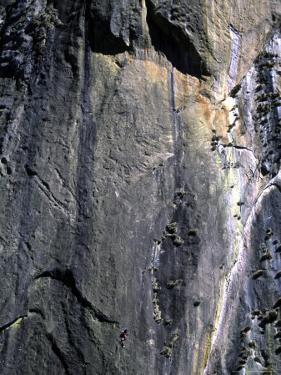 Climber Perched on Large Rock Wall, Madagascar by Michael Brown