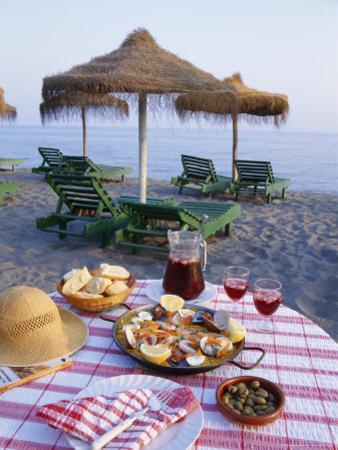 Paella with Olives, Bread and Sangria on a Table on the Beach in Andalucia, Spain by Michael Busselle