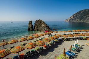 Beach umbrellas lining the beach in Monterosso al Mare, Cinque Terre, Italy. by Michael DeFreitas