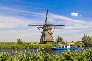 Canal tour boat and windmill in Unesco World Heritage Site, Kinderdijk, Holland, Netherlands. by Michael DeFreitas