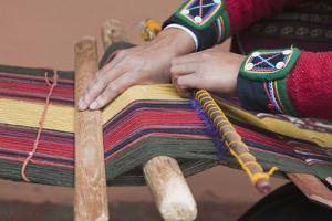 Peruvian woman in traditional dress at the local artisan coop workshop, Chincheros, Peru by Michael DeFreitas