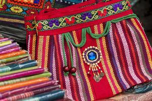 Traditional skirts, Souvenir bags. Dragon Spine Rice Terraces, Longsheng, China. by Michael DeFreitas