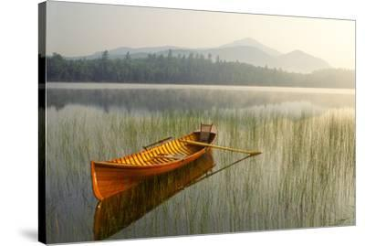 An Adirondack Guide Boat in a Calm Lake with Whiteface Mountain in the Background by Michael Forsberg