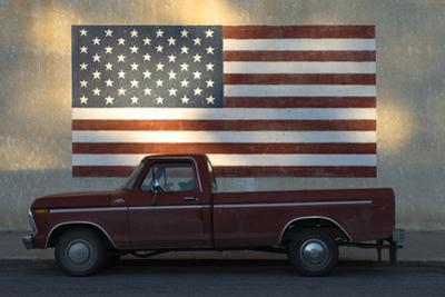 An Old Red Pickup Parked in Front of American Flag Mural by Michael Forsberg
