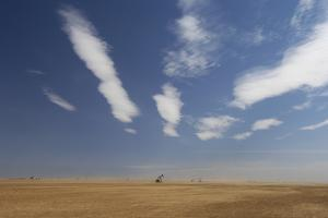 Oil Pump Jacks, Bare Ground, and Big Sky Stretch for Miles West of Leveland, Texas by Michael Forsberg