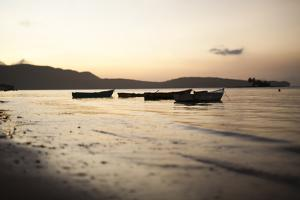 Empty Boats Float in the Calm Waters of the Dominican Republic at Dusk by Michael Hanson