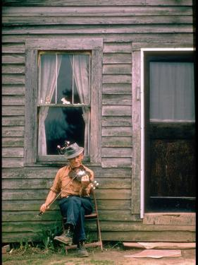 Country Musician, Fred Price, Sitting Outdoors in Front of Old House Playing the Fiddle by Michael Mauney
