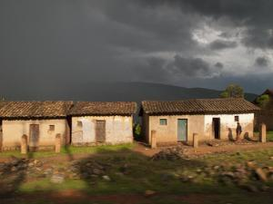 A Man Stands before Some Small Buildings as Rain Approaches by Michael Melford