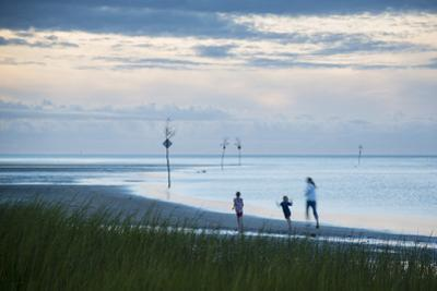 A Woman Jogging Along the Beach with Two Children in Rock Harbor, Orleans, Cape Cod by Michael Melford