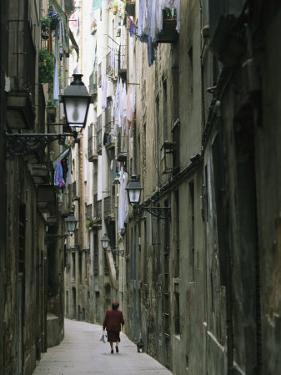A Woman Walking Along the Narrow Streets of Bracelona, Spain by Michael Melford
