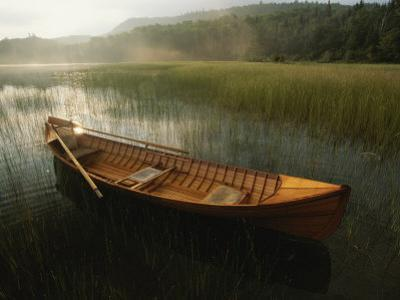 An Adirondack Guide Canoe Floating on Connery Pond at Sunrise by Michael Melford