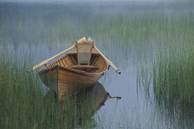 An Adirondack guide canoe floating on Connery Pond at sunrise. by Michael Melford