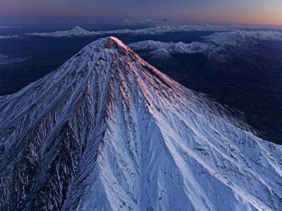 Kronotsky Volcano towers above nearby peaks, tundra, and forest by Michael Melford