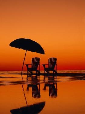 Picturesque Scene with Two Chairs and an Umbrella on the Beach by Michael Melford