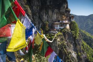 Prayer Flags Span the Chasm before the Tiger's Nest Monastery by Michael Melford