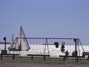 Sailboat and Kids on a Swing at a Playground at Sept-Iles, Quebec by Michael Melford