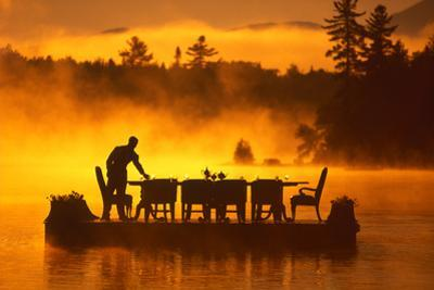 Silhouetted waiter setting a table on floating dining room at sunrise. by Michael Melford