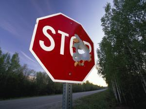 Stop Sign with a Large Bullet Hole by Michael Melford