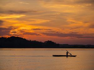 Young man paddling his fishing boat at sunset over calm waters on Clavero Lake, Amazon Basin, Peru by Michael Nolan