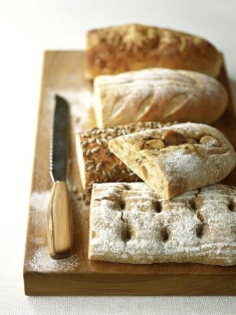 Assorted Loaves on Wooden Chopping Board by Michael Paul