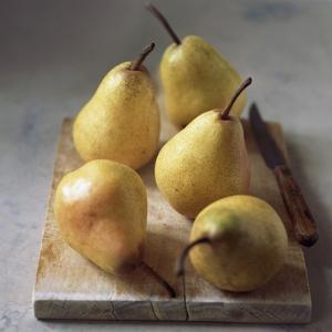 Five Yellow Pears on a Chopping Board by Michael Paul