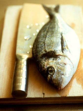 Gilthead Bream on a Wooden Board with Cleaver by Michael Paul