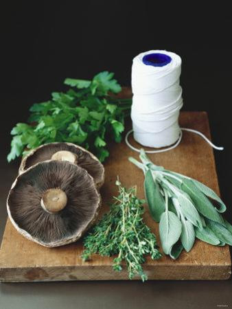 Mushrooms, Fresh Herbs & Kitchen String on Chopping Board by Michael Paul