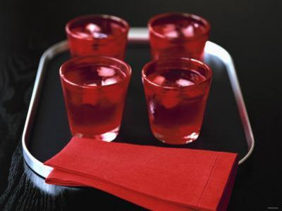 Water and Ice Cubes in Red Glasses on Tray by Michael Paul