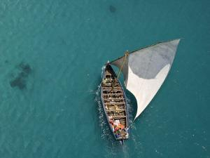 Aerial Shot of a Dhow Sailing in Turquoise Water by Michael Polzia