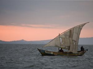 Dhow with a Tattered Sail Crosses Lake Victoria at Sunset by Michael Polzia