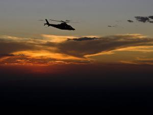 Helicopter Silhouetted Against a Dramatic Sky at Sunset by Michael Polzia