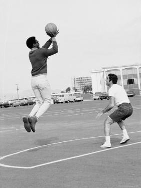 Comedian Bill Cosby Shooting Ball Against His Press Agent, Joe Sutton, During Game of Basketball by Michael Rougier