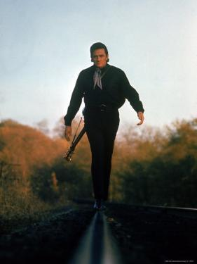 Country Music Star Johnny Cash Walking Along Line of Railway Track with His Guitar by Michael Rougier