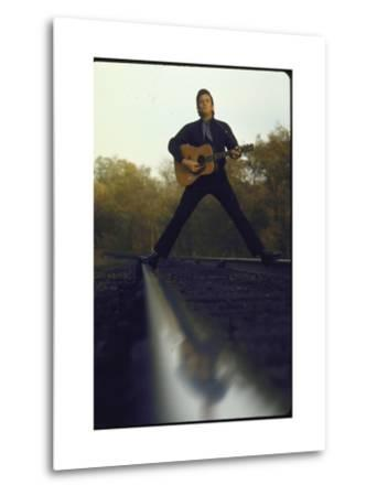 Country/Western Singer Johnny Cash with Guitar Straddling Railroad Tracks