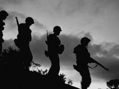 Four Soldiers with Helmets and Rifles Moving on Crest of Ridge, on Patrol at Night by Michael Rougier