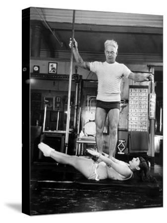 Opera Singer Roberta Peters Balancing Her Trainer, Joseph Pilates, on Her Operatic Breadbasket