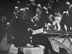 Sir Thomas Beecham Conducting Orchestra as Lady Beecham Plays Piano by Michael Rougier