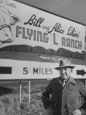 Super Rich Texas Millionaires William Likins Standing in Front of Sign at Main Entrance to Ranch by Michael Rougier