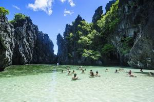 Tourists in the Hidden Bay with Clear Water in the Bacuit Archipelago, Palawan, Philippines by Michael Runkel