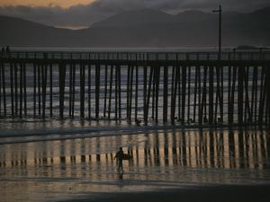 A Surfer Walks up the Beach Near a Pier at Twilight by Michael S. Lewis