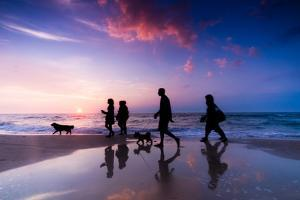 Family Walk on the Beach at Sunset by Michal Bednarek