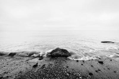 Nostalgic Sea. Waves Hitting in Rock in the Center. Black and White, far Horizon.