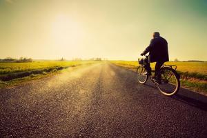 Old Man Riding A Bike On Asphalt Road Towards The Sunny Sunset Sky by Michal Bednarek