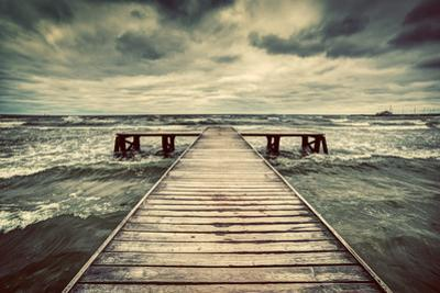 Old Wooden Jetty, Pier, during Storm on the Sea. Dramatic Sky with Dark, Heavy Clouds. Vintage by Michal Bednarek