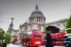 St Paul's Cathedral in London, the Uk. Red Buses in Motion and Man Walking with Umbrella. by Michal Bednarek