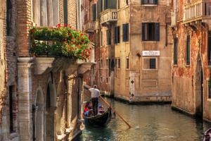 Venice, Italy. A Romantic Gondola Floats on a Narrow Canal among Old Venetian Architecture by Michal Bednarek