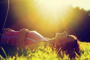 Young Pretty Woman Lying on the Grass at Summer Sunset by Michal Bednarek
